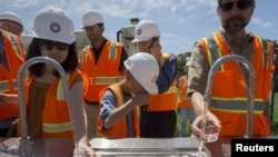 FILE - People taste recycled wastewater at the Edward C. Little Water Recycling Facility during the West Basin Municipal Water District's tour of a water recycling facility in El Segundo, California, July 11, 2015. More than 80 percent of wastewater worldwide is released without treatment, contaminating rivers and lakes, a U.N. report finds.