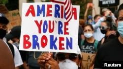 Seorang pengunjuk rasa membawa poster di Plaza Black Lives Matter dekat Gedung Putih dalam unjuk rasa memprotes diskriminasi rasial di Washington D.C, Sabtu, 6 Juni 2020, setelah kematian pria Afrika-Amerika, George Floyd, di Minneapolis saat ditahan poli