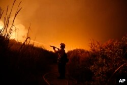 Firefighter Ryan Spencer battles a wildfire as it burns along a hillside toward homes in La Conchita, California, Dec. 7, 2017.