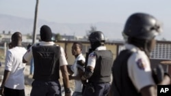 Police officers detain two demonstrators during a protest at the Cite Soleil slum in Port-au-Prince, Haiti, December 24, 2011.