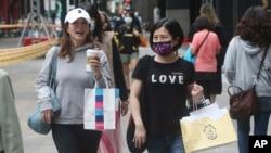 为防疫戴口罩的台湾民众走过台北的购物街区。(2020年10月29日)