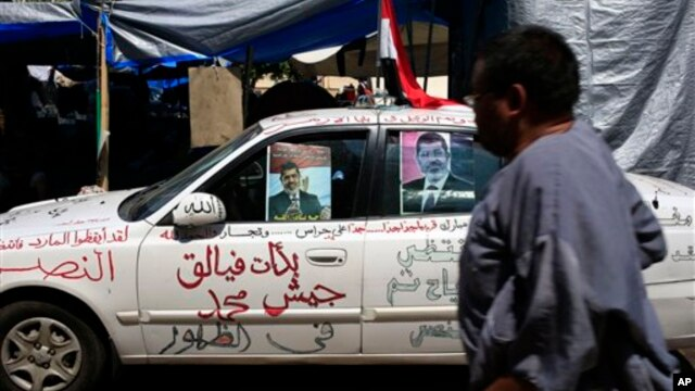 "A supporter of Egypt's Islamist President Mohamed Morsi walks past a car with Arabic in the middle that reads, ""Mohamed army corps began to emerge"" at Nasr City, where protesters have installed their camp and hold their daily rally, in Cairo, Egypt, July"