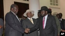Riek Machar, ancien vice-président du Soudan du Sud, salue le président sud-soudanais Salva Kiir, a droite, sous le regard du président ougandais Yoweri Museveni lors d'une réunion de sécurité à Entebe, Ouganda, 7 juillet 2018.