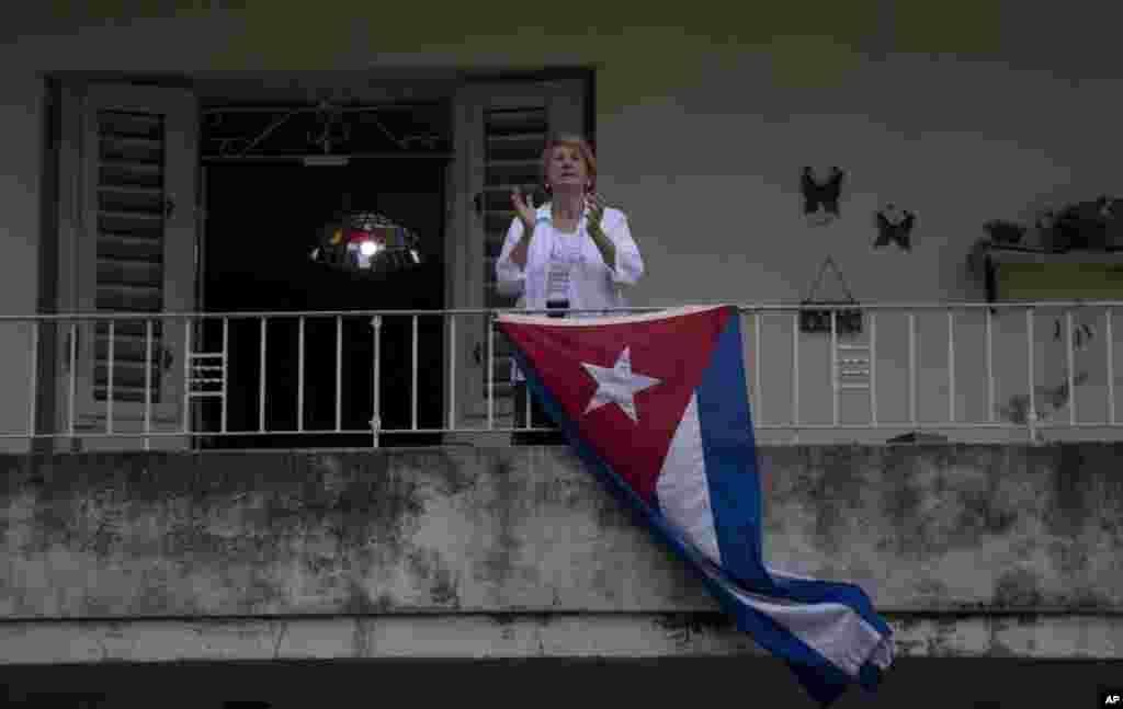 زن کوبایی از بالکنخانهاش برای همراهی در روز جهانی کارگر برای کارگران دست میزند. به خاطر شیوع کرونا، دولت کوبا هرگونه تجمع روز کارگر را لغو کرد.