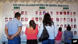 FILE - Photographs of the missing are on display at the future site of the Victims' City in Iguala, Guerrero State, Mexico, Nov. 22, 2016.
