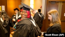 Mariama Bassama is helped with her hood by Charlotte Pandraud before the 2016 graduation ceremony for Hult International Business School, in Boston.