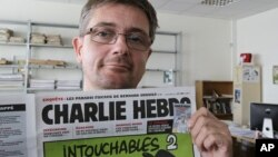 El director de la revista satírica Charlie Hebdo, Charb, muestra la portada de la publicación que presenta caricaturas de Mahoma desnudo.
