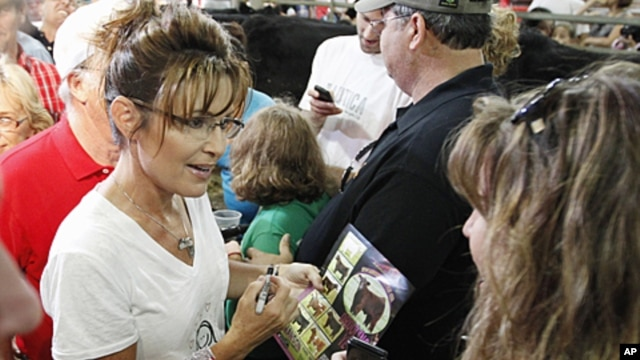 Former Alaska Governor Sarah Palin stops in the Cattle Tent as she visits at the Iowa State Fair in Des Moines, Iowa, August 12, 2011