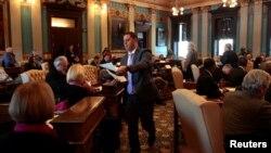 미시건주 대통령 선거인단 16명이 19일 랜싱의 주상원 회의실에서 투표용지를 배부받고 있다.