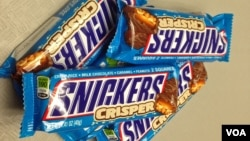 A display of chewy chocolate, caramel and peanuts Snickers bars. Confectionery maker Mars has issued a recall of its candy bars across Europe over fears that plastic pieces could be found inside. The recall covers 55 countries, Feb. 23, 2016. (D. Bekheet/VOA)
