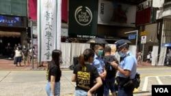 多名軍裝警員9月5日中午在港大學生會擺街站,派發反全民檢測單張前,截查負責街站的港大學生會成員。(美國之音 湯惠芸拍攝)
