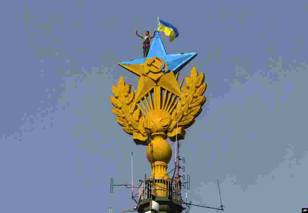 A worker takes a selfie before removing a yellow and blue Ukrainian flag attached by protesters atop Stalin-era skyscraper in Moscow, Russia. Protesters scaled one of Moscow's famed Stalin-era skyscrapers and painted the Soviet star on its spire in the national colors of Ukraine.