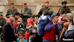 Syrian army soldiers (rear L) and Russian soldiers (rear R) look on as rebel fighters and their families evacuate the besieged Waer district in the central Syrian city of Homs, after an agreement was reached between rebels and Syria's army, March 18, 2017.