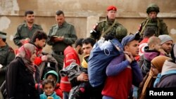 شام اور روس کے فوجی حمص کے علاقے الوائیر سے باغیوں کے انخلا کی نگرانی کررہے ہیں۔ فائل فوٹو