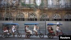 Para turis naik becak di Havana, Kuba (23/1).