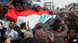 Anti government protesters carry a big Iraqi flag and chant anti Iran and anti U.S. slogans during the ongoing protests in Tahrir square, Baghdad, Iraq, Friday, Jan. 10, 2020.