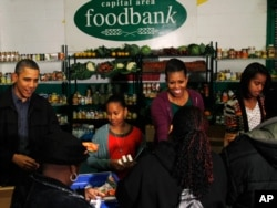 美国总统奥巴马的全家2011年在感恩节前夕在华盛顿一个为穷人提供食物的食品银行帮助发放食物