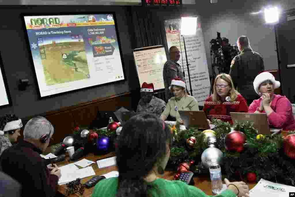 2012年12月24日,圣诞节前夕,在北美航空航天防务司令部(NORAD)的科罗拉多州斯普林斯的彼得森空军基地 ,志愿者接听孩子们打来的电话。儿童们询问圣诞老人到了哪里,何时把礼物送到他们家。志愿者回答他们。每年圣诞节前夜,NORAD的一千多名志愿者处理来自世界各地的儿童的十万多个电话,而NORAD则持续地预报圣诞老人送礼的行程。