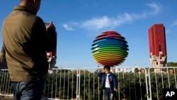 2014年11月6日,一名男孩在APEC北京峰會標誌附近拍照。為了能讓與會者呼吸到更清新的空氣,中國政府採取了一系列強制措施。