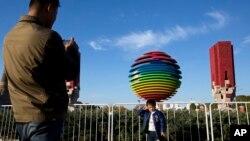 2014年11月6日,一名男孩在APEC北京峰会标志附近拍照。为了能让与会者呼吸到更清新的空气,中国政府采取了一系列强制措施。