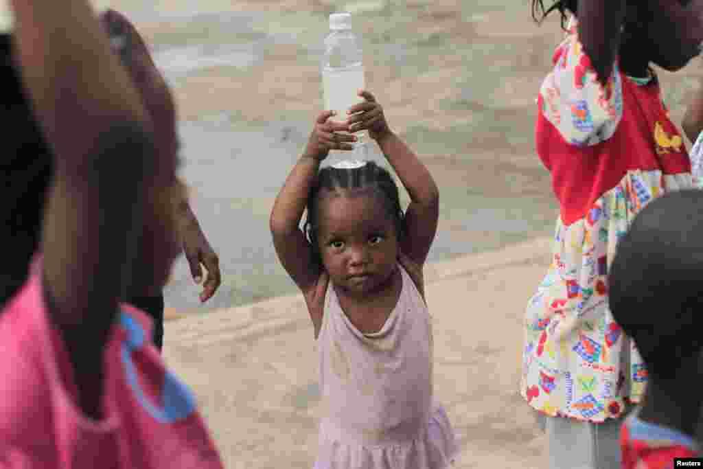 ایک بچی نے پانی کی بوتل اٹھا رکھی ہے
