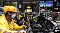 美团快递的快递员们正准备把一家北京餐馆的午餐饭盒送出。(2021年4月27日)