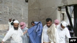 Nhiều người đem các mảnh thân thể còn lại của 1 xác nạn nhân trong vụ nổ khỏi xưởng chế tạo vũ khí ở 1 thành phố miền nam Yemen, 28/3/2011