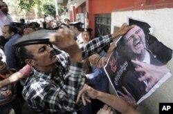 Manifestante destroi com a ajuda de sapato uma fotografia do presidente Bashar al-Assad