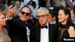 FILE - A guest takes a selfie with director Woody Allen (C) and his wife Soon-Yi Previn as they arrive on the red carpet at the 68th Cannes Film Festival in Cannes, southern France, May 15, 2015.
