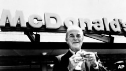 Ray A. Kroc, founder of McDonald's Corporation, is shown holding a hamburger in front of a McDonald's restaurant at an unknown location in this undated photo.