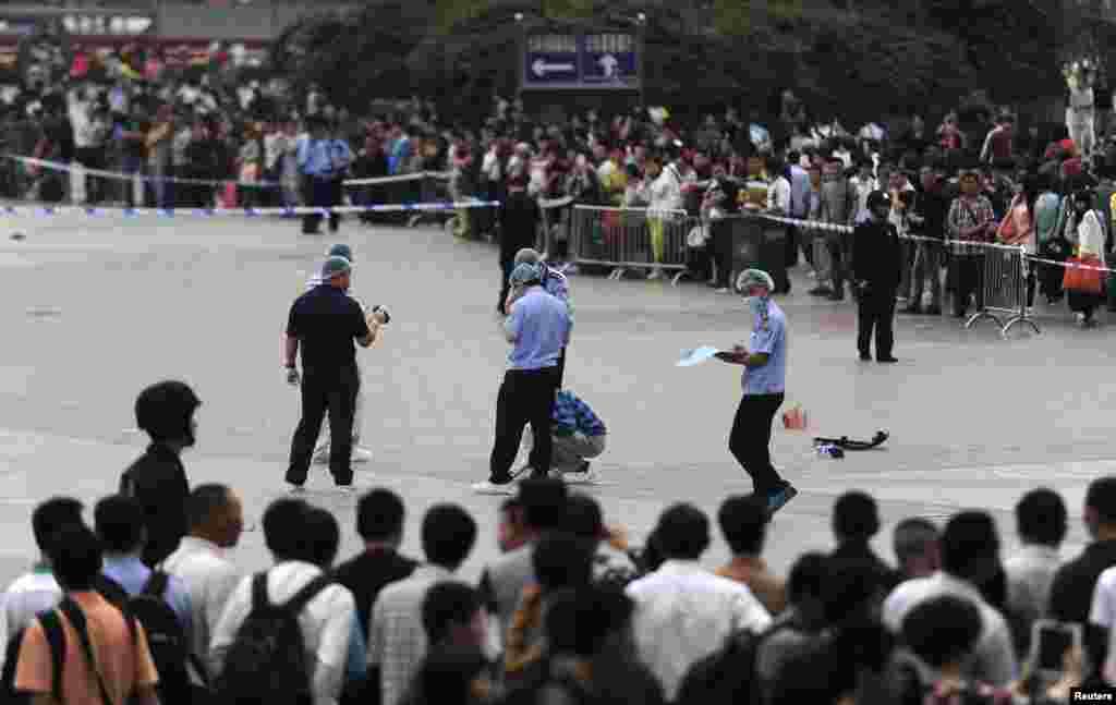 Politsiya Xitoyning Guanchjou shahridagi poyezd stansiyasida pichoq bilan chavaqlash hodisasi yuz bergan joyni ko'zdan kechirmoqda. Hujumda kamida 6 kishi jarohat olgan, 6-may, 2014-yil.