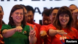 FILE - Davao City Mayor Sara Duterte-Carpio (L) and Ilocos Norte Governor Imee Marcos gestures during an alliance meeting with local political parties in Paranaque, Metro Manila in Philippines, Aug. 13, 2018.