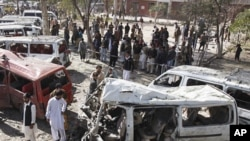 People visit the site of a bomb blast at a bus station in Peshawar, Pakistan, February 23, 2012.