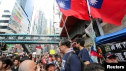 Taiwan flags are seen near protesters attending a demonstration to demand the resignation of Hong Kong leader Carrie Lam and the withdrawal of the extradition bill, in Hong Kong, China June 16, 2019. REUTERS/James Pomfret