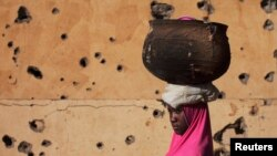 A girl walks by a building pockmarked with bullet holes from fighting in Gao, Mali, Mar. 13 2013.