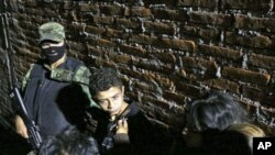 """Edgar Jimenez Lugo (C) alias """"El Ponchis"""" talks to a journalist as he is presented to the media in Cuernavaca. Soldiers arrested the teen suspected drug gang hitman Jimenez in central Mexico as he attempted to travel to the United States, (File)"""
