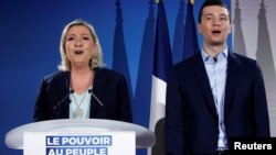 French far-right National Rally (Rassemblement National) party leader Marine Le Pen and Jordan Bardella, the head of the National Rally list for the European elections, sing the national anthem during a meeting in Saint-Paul-du-Bois, France, Feb. 17, 2019