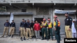Policemen and rescue workers gather outside a building where unidentified gunmen killed police cadets in Lahore on July 12, 2012.