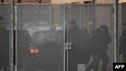Один из четверых подозреваемых в окружении полицейского эскорта