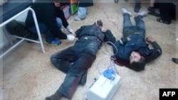 1 bác sĩ Syria, trái, chữa trị cho những người bị thương vì pháo kích của quân đội Syria ở Baba Amr, Homs, 26/12/2011
