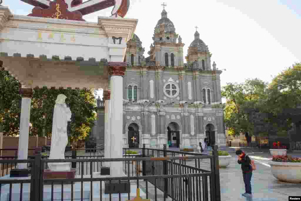 """一位信徒2018年10月1日在北京的圣约瑟夫教堂外祈祷,这是一个政府认可的天主教堂,又叫王府井天主堂。在梵蒂冈和中国签署历史性的主教任命协议后,罗马天主教教宗方济各9月26日在写给中国教徒的信中敦促他们相信新协议是为了所有中国天主教徒的利益。教宗还敦促中国政府以""""信任、勇气和远见""""来继续两国间的对话。"""