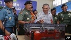 Miembros de las Fuerzas Armadas indonesias muestran una de las cajas negras del vuelo 8501 de AirAsia. Ambas grabadoras han sido encontradas y están siendo analizadas.
