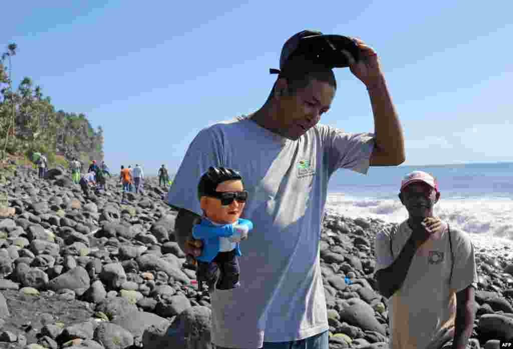 An employee of an environmental protection and coastal cleanup organization shows a figurine of South Korean singer Psy found during a search for debris from the ill-fated Malaysia Airlines flight MH370 on a beach in Sainte-Marie de la Reunion, between Champ Borne and the Rivière du Mât river, on the French Reunion Island in the Indian Ocean.