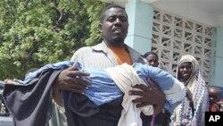 图为一名南部索马里男子7月25日从医院抱走死去孩子的遗体