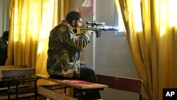 A Syrian rebel aims his rifle inside a classroom at a school in the Deir Baalbeh neighborhood in Homs province, Syria, February 22, 2012.