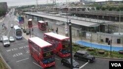 Autobuses frente a una estación de Londres, con el parque olimpico al fondo.