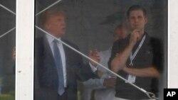 El presidente Donald Trump habla con su hijo Eric, mientras ve la segunda ronda del Torneo Abierto de Golf de Mujeres que se desarrolla en su club de Bedminister, New Jersey.