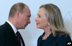 Russian President Vladimir Putin, left, speaks to U.S. Secretary of State Hillary Rodham Clinton on her arrival at the APEC summit in Vladivostok, Russia, Sept. 8, 2012.