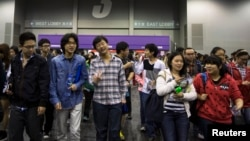 In this 2013 photo, students leave after a college entrance test at AsiaWorld-Expo in Hong Kong.