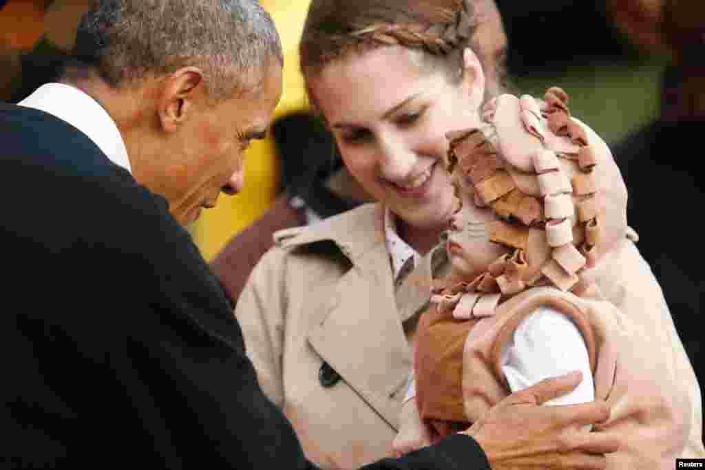 2014年的白宫万圣节活动中,奥巴马总统迎接穿着狮子服装的儿童